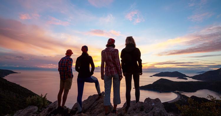 Pessoas a caminhar na montanha e a olhar para o mar num pôr do sol