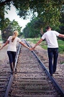 Casal, de mãos dadas, a caminhar nos carris de uma linha de comboio
