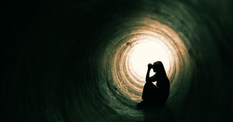 Mulher com ar depressivo sentada ao fundo do túnel com as mãos unidas junto à testa