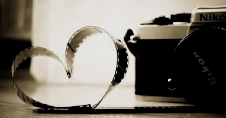 Legenda de imagem: Máquina fotográfica e fita em formato de coração